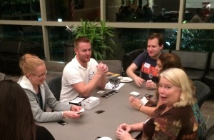 Dr. Dustin Shepler (middle, white shirt) leads a card game with students and some of their family members at the most recent Game Night held at MSP.