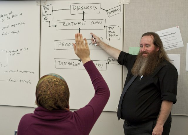 Photo of instructor at a whiteboard pointing at some writing and a student in the auidence with their hand up.