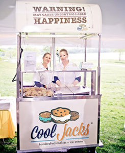 Two women standing behind an ice cream cart with Cool Jacks logo.