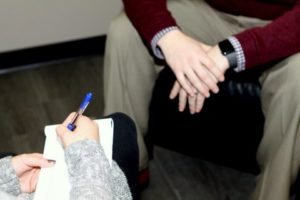 Image of hands. One set writing with a pen and holding a pad of paper. Another person with hands clasped sitting acrossed from each other.