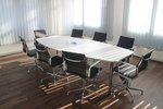 Stock photo of a conference room. White table in the middle of the room with 8 black office chairs around it.