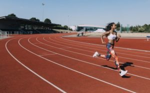 Photo of a young woman running on a outdoor track.