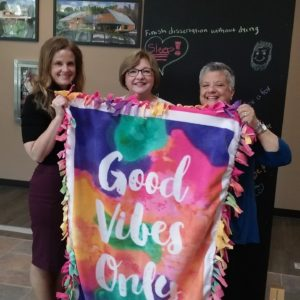 Amanda, Denene, and Fran hold a blanket.