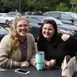 Two students sitting at a table during Welcome Week BBQ.