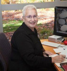 Photo of Dr. Diane Blau sitting behind her desk in her office.