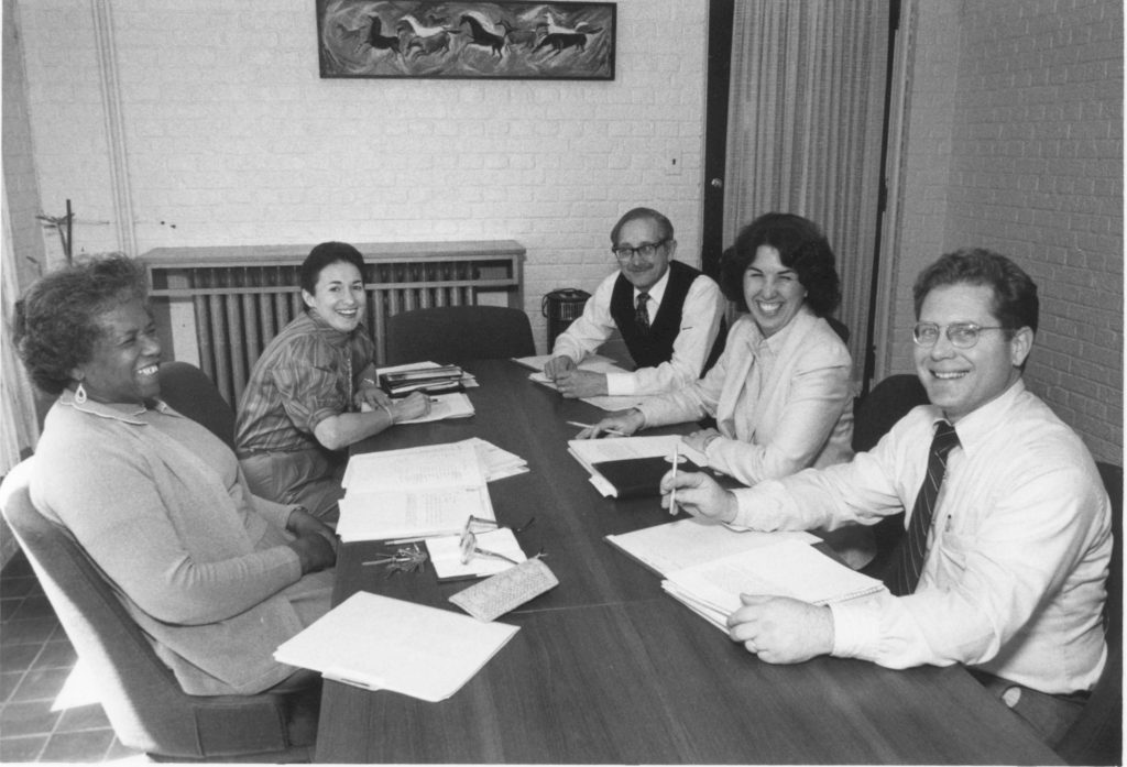 Black and white photo of early faculty meeting at CHS. From left: Cereta Perry, Diane Blau, Clark Moustakas, Mary Erlandson, and Bruce Douglass
