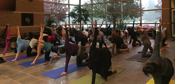 People doing yoga pose simultaneously in atrium.
