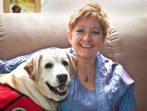Photo of Dr. Betz King and her dog, a yellow lab named Paisley, wearing a red therapy dog vest.