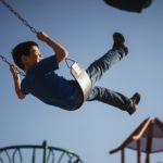 Child swinging high on a swing.