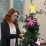 Student standing beside holiday giving tree.