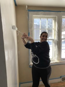 Student smiling while painting a wall.
