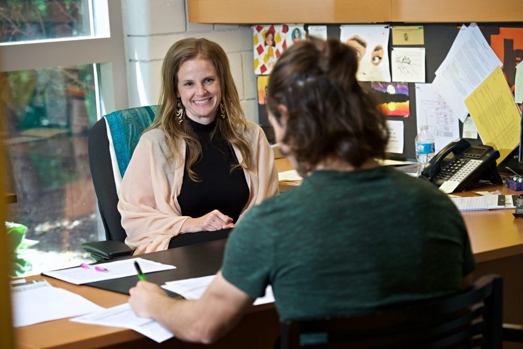 Photo of the Registrar meeting with a student in an office.