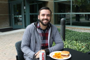 Student smiling next to his lunch at the BBQ.