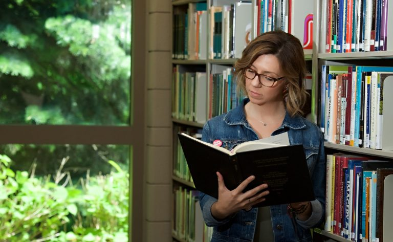 Photo of a woman leaning against a bookshelf full of books in the library reading from a book.