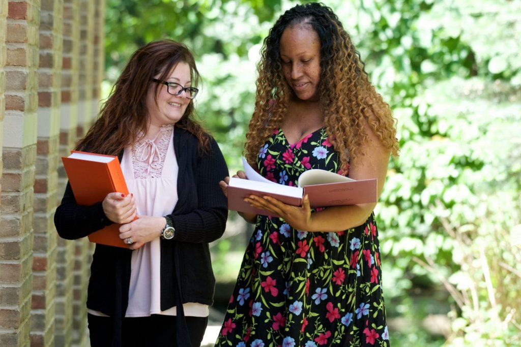 Photo of two women standing together outside next to a brick wall with trees in the background. One woman has a book open ans is looking at it. The other woman is holding a book in her arms and smiling. She is looking over at the woman holding the book open.