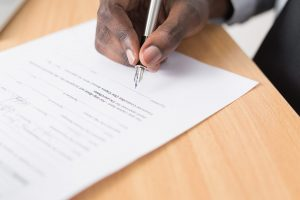 Photo of a person's hand holding a pen and signing a document.