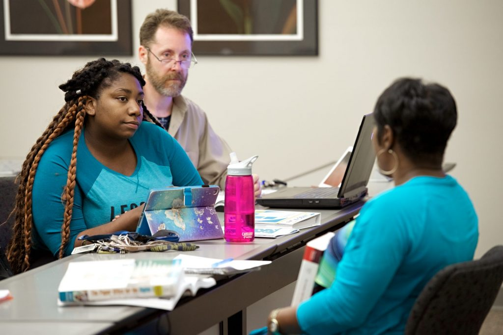 Image of Dr. Gaines teaching with two students listening.