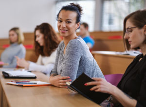 Stock photo of a woman in a classroom smiling.