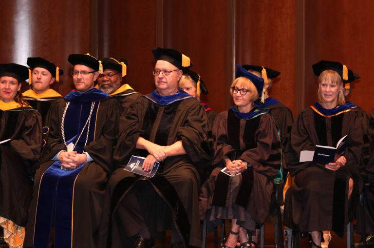 Photo of MSP faculty in graduation regalia sitting on a stage during graduation.