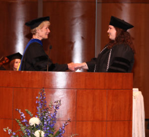 Photo of faculty member shaking hands with student on stage at graduation. Both persons are wearing graduation regalia.