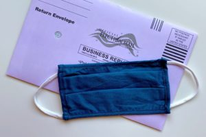 Photo of a mask laying on top of a ballot envelope.