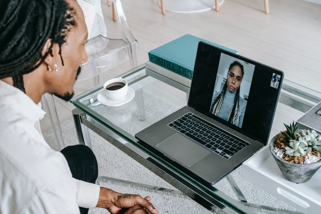 Stock photo of male presenting person in a telehealth session with a female presenting person on a laptop.