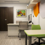 Photo of the interior of the Michigan School Psychological Clinic applied behavior analysis (ABA) clinic. Small children's sized tables and chairs. Larger desk for adults to meet at.