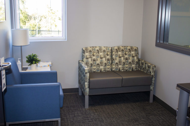 Photo of the interior of the Michigan School Psychological Clinic. Office with a small, patterned couch and armchair.
