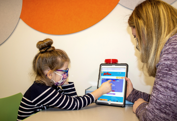 Photo of clinician working in the ABA clinic with a child using an ipad.