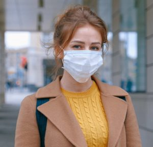 Photo of a woman wearing a backpack and a face mask.