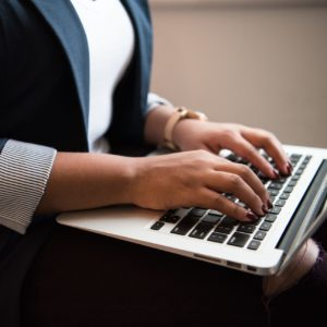 Stock photo- close up image of person typing on laptop, balanced on their lap