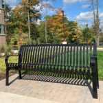 Photo of black bench with brick pavers under the bench